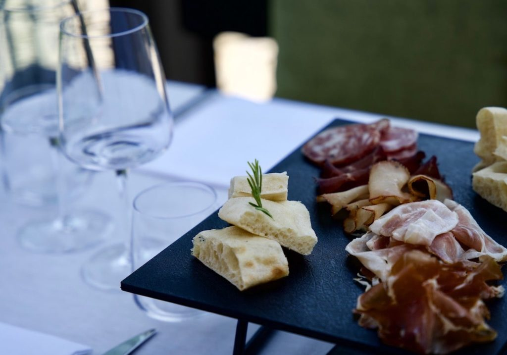 Allestimento tavolo ristorante Bellagio con focaccia, salame, prosciutto crudo, prosciutto